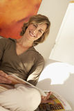 Blonde woman relaxing at home, reading magazine, smiling, portrait (tilt) Stock Photo