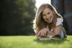 Blonde woman relaxing on lawn in garden, lying on front, reading book, smiling, front view, portrait, surface level (differential  Royalty Free Stock Photos