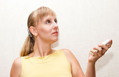 Blonde woman with remote. Blonde woman with wihte remote in hand Royalty Free Stock Photo