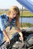 Blonde woman repairs car motor Royalty Free Stock Photography