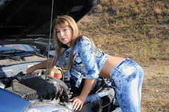 Blonde woman repairs car motor Royalty Free Stock Images