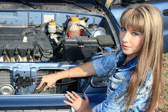 Blonde woman repairs car motor Royalty Free Stock Photo