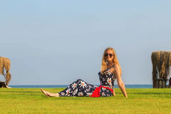 Blonde woman resting on lawn near sea. Stock Photography