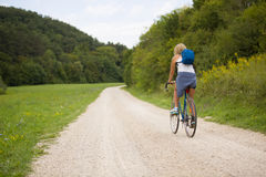 Blonde woman ride bicycle outdoor, next to a forest Stock Photos