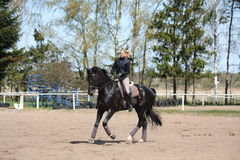 Blonde woman riding black horse Stock Images