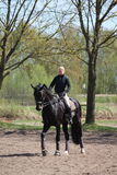 Blonde woman riding black horse Royalty Free Stock Image