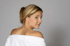 Blonde Woman in Robe Looking Over Shoulder. Young Blonde Woman in Robe Looking Over Shoulder Stock Photos