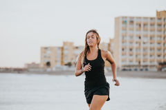 Blonde woman running in the beach with black sportswear. royalty free stock images