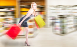 Blonde woman running in a shopping spree. With a out of focus shop in the background Stock Image