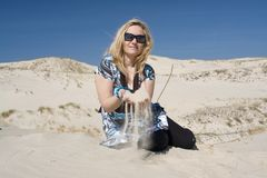 Blonde Woman on Sand Dune. Blonde woman sitting in white sand, dunes in background, sifting sand through her hands, wearing sunglasses, bright sunshine Stock Photos