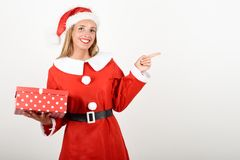 Blonde woman in Santa Claus clothes smiling with gift box. Blonde woman in Santa Claus clothes smiling with gift box in her hands. Young female with blue eyes Stock Images