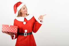 Blonde woman in Santa Claus clothes smiling with gift box. Blonde woman in Santa Claus clothes smiling with gift box in her hands. Young female with blue eyes Royalty Free Stock Photos