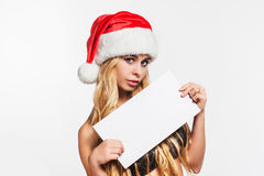Blonde woman in Santa hat holding leaflet for message Stock Photography