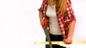 Blonde woman sawing a wood plank Royalty Free Stock Photo