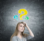 Blonde woman scratching head, question marks Royalty Free Stock Image
