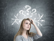 Blonde woman scratching head, questions, arrows stock image