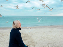 Blonde woman and seagulls in cloudy autumn day Royalty Free Stock Photography