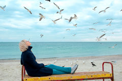 Blonde woman and seagulls in cloudy autumn day Stock Photo