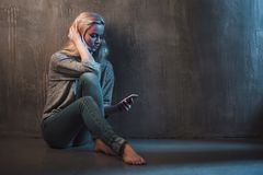 Blonde woman searching info with her smartphone. Young woman sitting on the floor and using her telephone, gray background royalty free stock photo