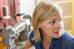 Blonde Woman At Sewing Machine Royalty Free Stock Photos