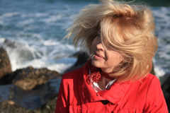 Blonde woman shaking head near sea Stock Images