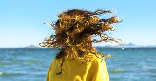 Blonde woman shakes head with curly hair at the beach stock photo