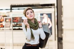 Blonde woman with shopping bags in one hand and credit card in another in mall royalty free stock photos