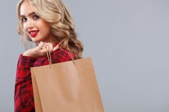 Blonde woman at shopping holding bag isolated on gray background on black friday holiday. Concept for sale ads. Royalty Free Stock Photography