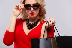 Blonde woman at shopping holding dark bag  on gray background on black friday holiday. Concept for sale ads. Stock Images