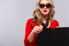 Blonde woman at shopping holding dark bag  on gray background on black friday holiday. Copy space for sale ads. Stock Image