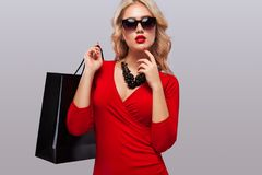 Blonde woman at shopping holding dark bag isolated on gray background on black friday holiday. Copy space for sale ads. Stock Image