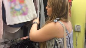 A blonde woman shops in a clothing department store - Close up. June 24 2018 stock video