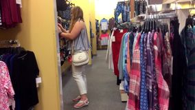 A blonde woman shops in a clothing department store. June 24 2018 stock video
