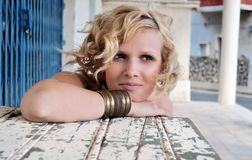 Blonde woman with short curly hair caught in the gust of wind. Royalty Free Stock Image