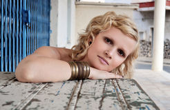 Blonde woman with short curly hair sitting behind an old table. Stock Image