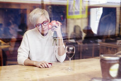 Blonde woman with short hair and eye glasses sitting in a cafe or restaurant near window. Romantic mood, present and flowers in ha Stock Images