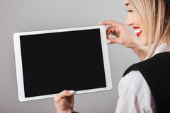 Blonde woman showing empty screen tablet computer. Gray background. You can place your text information, image or logo Stock Photo