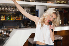 Blonde woman singing and dancing with hand up Stock Photography