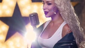 Blonde woman Singing with Retro Microphone. slow. Singing Woman with Retro Microphone. female jazz singer with microphone, music hall, the scene, shining star in stock video footage