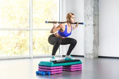 Blonde woman sit-ups, squad on step platform with barbell. Studio shot Royalty Free Stock Photos