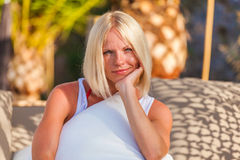 Blonde woman siting on deckchair, enjoying summer holidays. Royalty Free Stock Photos