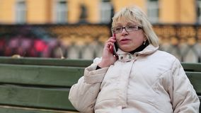 Blonde woman sits on the bench and talks on the phone stock video