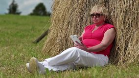 Blonde woman sits on a green grass near haystack and uses smartphone stock footage