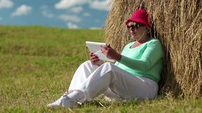 Blonde woman sits on a green grass near haystack and uses tablet PC stock video footage