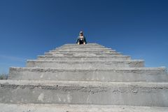 Blonde woman sits on top of concrete stairs platform against a blue sky. Negative space composition, with lots of copyspace for royalty free stock image