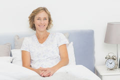 Blonde woman sitting in bed smiling at camera Stock Photography