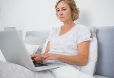 Blonde woman sitting in bed using laptop Royalty Free Stock Images