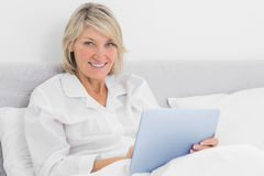 Blonde woman sitting in bed using tablet pc Royalty Free Stock Photo
