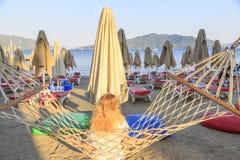 Blonde woman sitting on hammock among sunbeds and enjoying beach royalty free stock photo
