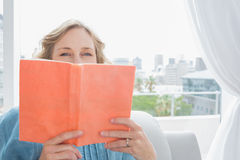 Blonde woman sitting on her couch covering face with orange book Stock Photos